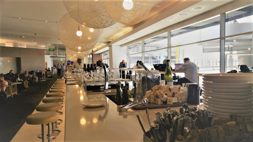 Take a seat at the long bar and look out of the floor to ceiling windows at the Qantas business lounge at Sydney International